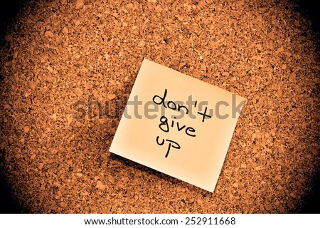 Cork notice board with one pink sticky note pad - motive - do not give up - stock photo