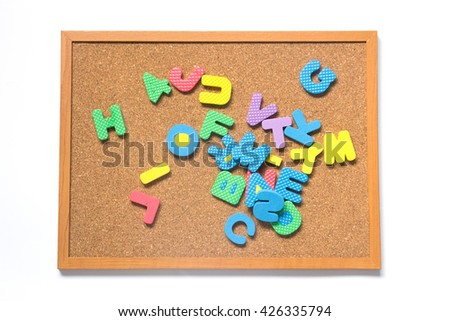 Corkboard with pile toy alphabet and number placed on white background - stock photo