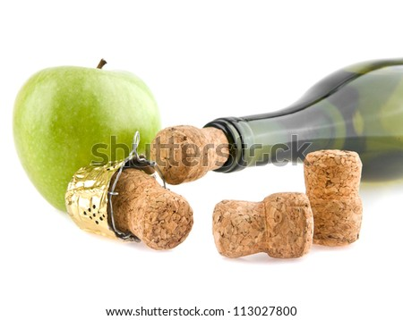 corks, apple and bottle of champagne on a white background - stock photo