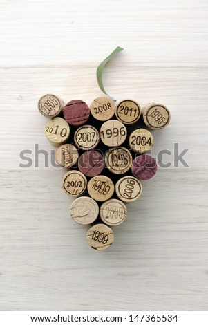 Corks in grape shape on white wood - stock photo