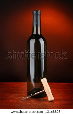 Corkscrew and bottle of wine on wooden table, on dark background - stock photo