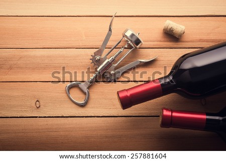 Corkscrew and wine bottles on wooden table. Top view. - stock photo