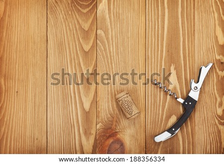 Corkscrew and wine cork on wooden table background with copy space - stock photo
