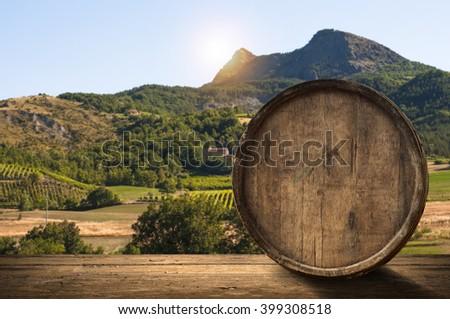 corkscrew and wooden barrel, vineyard on background - stock photo