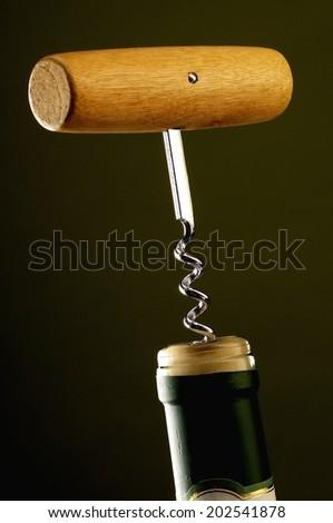 Corkscrew, classic wooden handle, deep green background. Portrait format. - stock photo