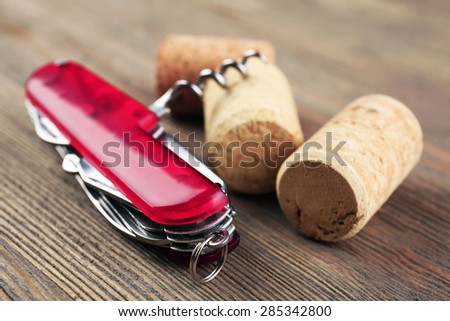 Corkscrew with corks on wooden table close up - stock photo
