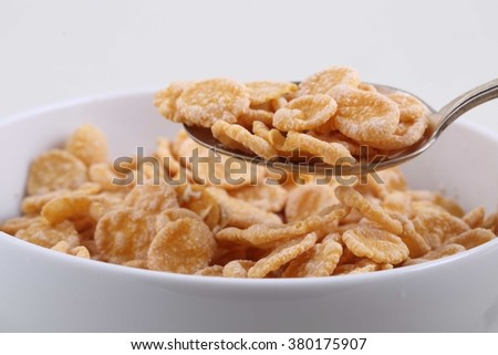Corn and rice flakes in a spoon on a white background