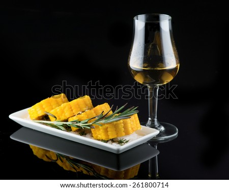 corn baked in the oven with a glass of cognac - stock photo