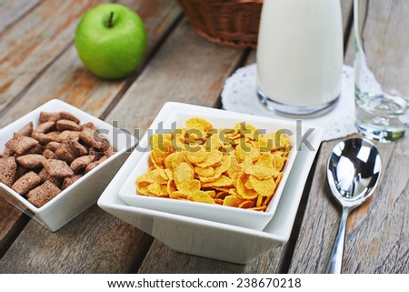 corn cereal with fresh milk and green apples on a wooden table