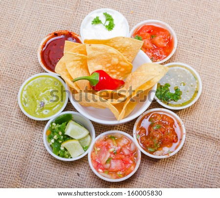 Corn chips served with assorted salsas. - stock photo