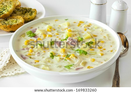 Corn Chowder - creamy corn chowder with ham and potatoes, served with crunchy garlic bread. - stock photo
