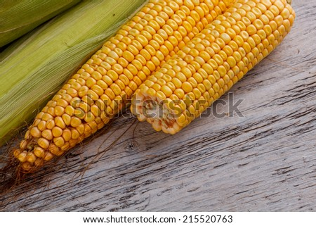 Corn cob and green leaves on wooden background