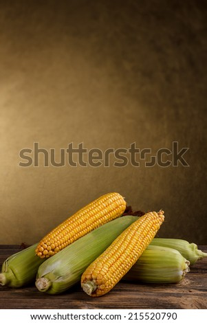 Corn cob on old wooden table - stock photo