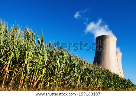 Corn field against nuclear power plant Conceptual image