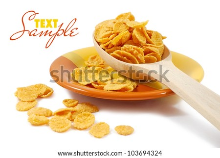 Corn flakes and wooden spoon on a dish isolated on white - stock photo