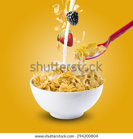 Corn Flakes Falling On Milk Splash With Berries and Red Spoon. Health Breakfast - stock photo