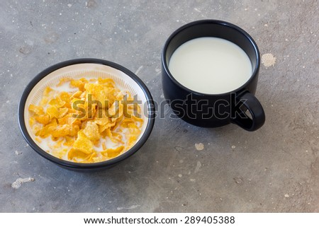 Corn flakes heap in a glass bowl and milk in black mug on concrete - stock photo