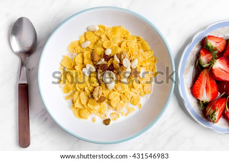Corn flakes with berries and nuts on a marble table