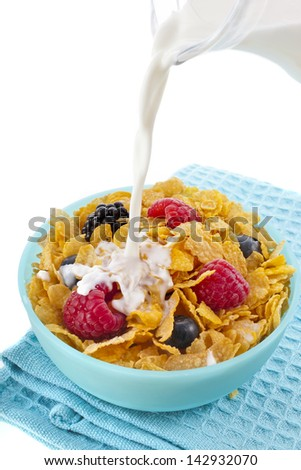 corn flakes with fresh berries and pouring milk isolated on white background - stock photo