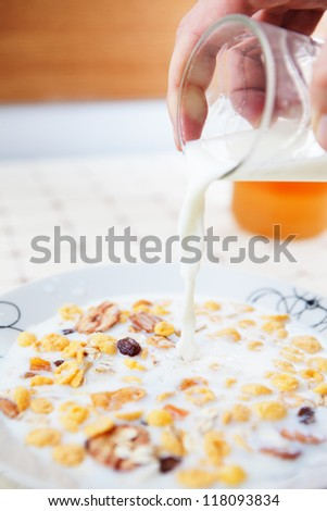 Corn flakes with milk pouring from glass - stock photo
