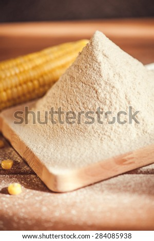 corn flour and corn on the cob on a wooden table - stock photo