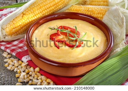 corn grits polenta in a bowl on old wooden table - stock photo