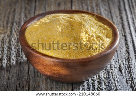 corn grits polenta in a wooden bowl on old wooden table - stock photo