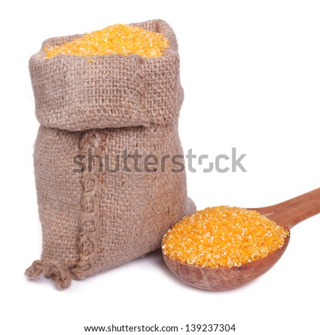 Corn groats in a bag and a wooden spoon isolated on a white background - stock photo