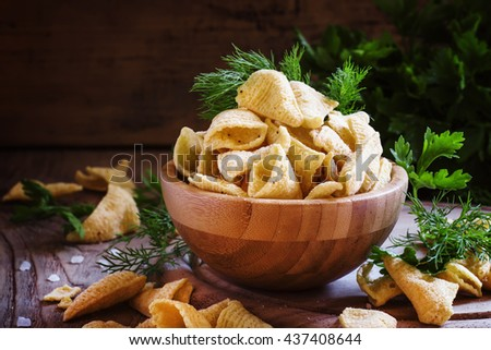 Corn nachos chips in the form of cones, with salt and dill, vintage wooden background, selective focus - stock photo