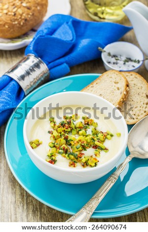 Corn soup with eggs and peppers garnished with vegetables and herbs in a white plate on a wooden background with dark blue napkin and spoon. selective Focus - stock photo