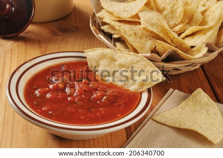 Corn tortilla chips and a dish of salsa on a rustic wooden counter