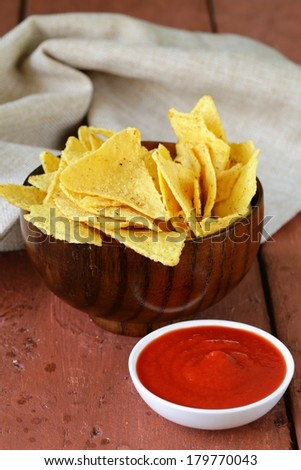 corn tortilla chips in a bowl with tomato sauce