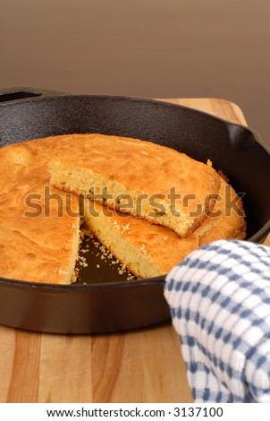 Cornbread in a cast iron skillet with piece cut out vertical view - stock photo