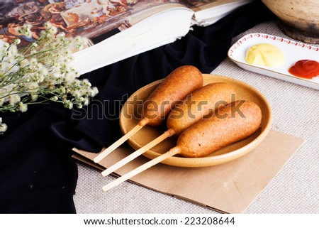 corndog sausage on a stick with mustard, ketchup and parsley - stock photo