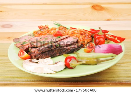 corned beef on plate with vegetables over wooden table
