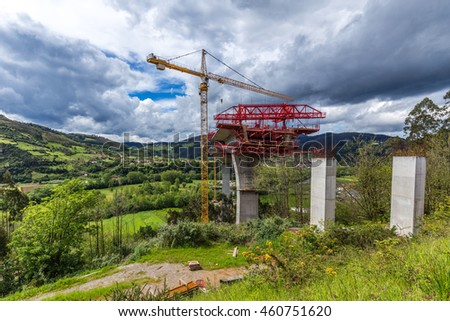 CORNELLANA, SPAIN MAY 12 2016: Construction crews are working on the highrise spans that will connect to highway A-63 near Cornellana, Spain.