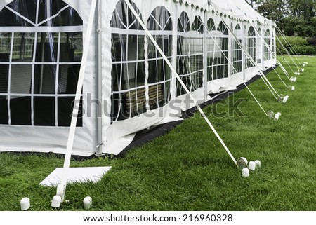 Corner and side of large white event tent with plastic windows, anchored on garden lawn in summer - stock photo