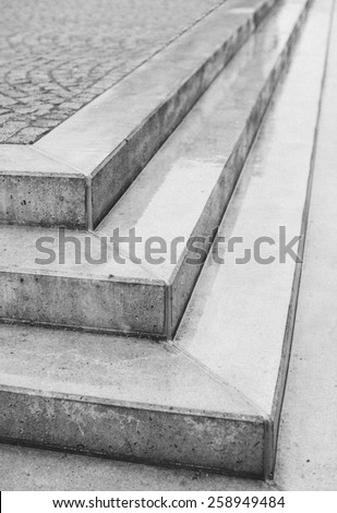Corner angle of three exterior concrete urban steps with cobblestones above in a street or courtyard with the point of the corner facing the camera in an architectural background