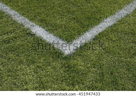 Corner boundary lines of a green grass sports field.