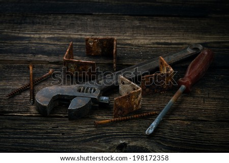 corner braces, screws, screwdriver and adjustable wrench on wooden background