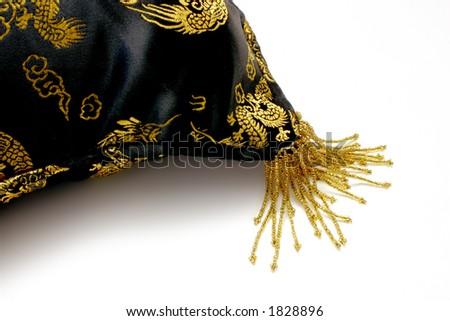Corner detail of Satin Chinese cushion with beaded fringe - stock photo