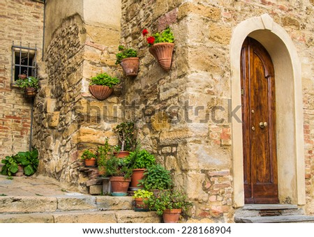 Corner in a Tuscany town with a lot of flowers and plants, just near a door entrance - stock photo