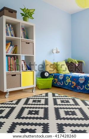 Corner of a blue teenager room with large rack on wheels, covered bed and patterned carpet - stock photo
