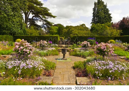Corner of a flagged English garden with stone vase.  - stock photo