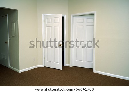 Corner of a large room showing two doors, one opening in and one opening out.