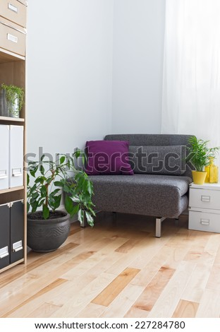 Corner of a living room with gray armchair, bookcase and plants. - stock photo