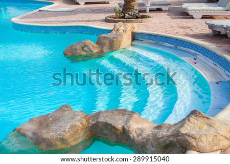 Corner of a swimming pool with decorative stones.