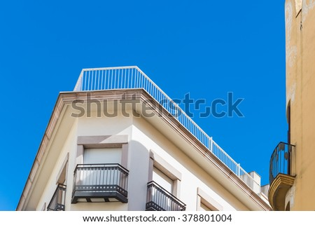 Corner of apartment building under blue sky  Corner detail view of apartment building with window shades down and railing on roof under blue sky - stock photo