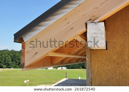 Corner of house with eaves against summer background. Install soffits. - stock photo