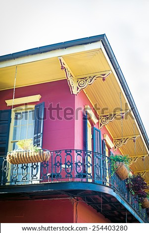 Corner of old red house with yellow eaves and black iron railing balcony in French Quarter of New Orleans, Louisiana, USA - stock photo